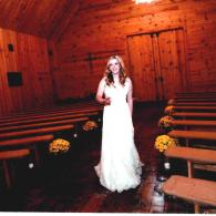 This beautiful bride stands before our venue surrounded by our long benches that can seat between 150-200 guests!